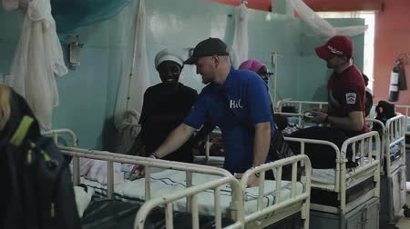 aids : KENYA, KISUMU - MAY 20, 2017: Caucasian men in African hospital talking with people. Volunteers helping to local people.