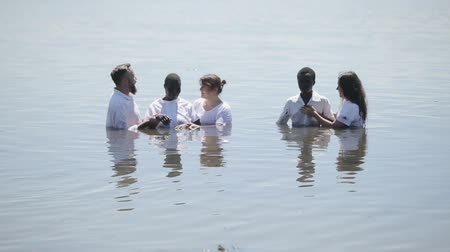 KENYA, KISUMU - MAY 20, 2017: Caucasian people baptize African people in white clothes in the water on shore of lake. Vídeos