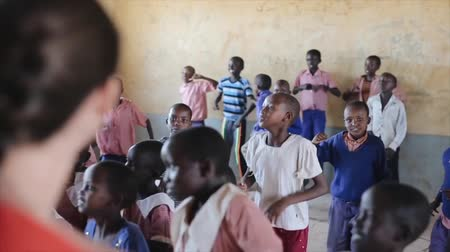 KENYA, KISUMU - MAY 20, 2017: Caucasian woman dancing with African children in local school, have fun