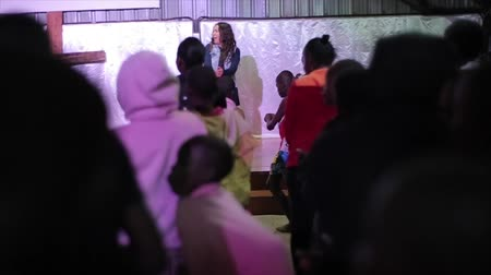 KENYA, KISUMU - MAY 20, 2017: Caucasian woman on the stage dancing, showing movements to big group of African children, boys and girls.