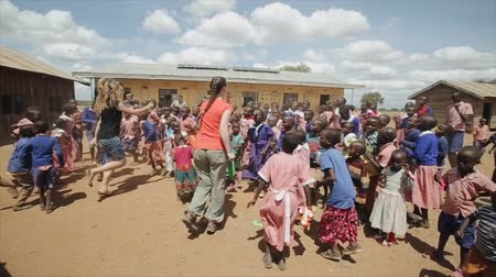 KENYA, KISUMU - MAY 20, 2017: Caucasian women dancing with African children outside the school building.