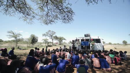 KENYA, KISUMU - MAY 20, 2017: Crowd of African children sitting on ground and listen Caucasian men and women.