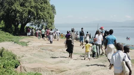 fete : KENYA, KISUMU - MAY 20, 2017: Group of african and caucasian people with children walking on the shore of the sea. Stock Footage