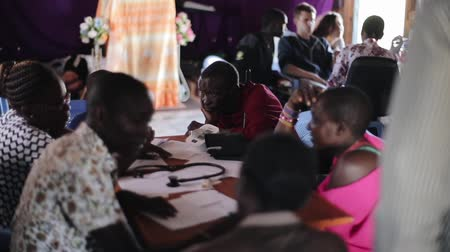 KENYA, KISUMU - MAY 20, 2017: Group of African people sitting inside, at the table and talking with doctors. Vídeos