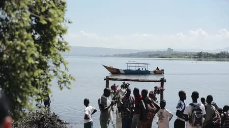 fete : KENYA, KISUMU - MAY 20, 2017: Group of african people, teenagers on the shore of the sea in sunny summer day.