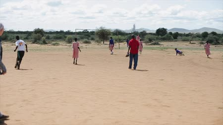 KENYA, KISUMU - MAY 20, 2017: Happy African children and Caucasian people playing football outside together. Vídeos