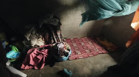 KENYA, KISUMU - MAY 20, 2017: Inside a poor little house in Africa. A lot of clothes, linen lies on the concrete floor. Vídeos