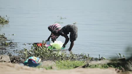KENYA, KISUMU - MAY 20, 2017: Two african women staying on the shore of the lake and washing dishes together. Vídeos