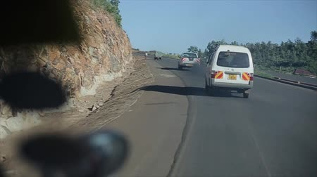 KENYA, KISUMU - MAY 20, 2017: View from inside a moving car. Automobile is riding through the country road, turns on serpentine in bright sunny day in Africa.