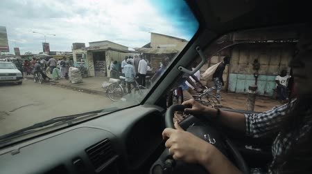 flama : KENYA, KISUMU - MAY 20, 2017: View through the windshield from inside a car.Woman is driving through the city in Africa in sinny bright day.