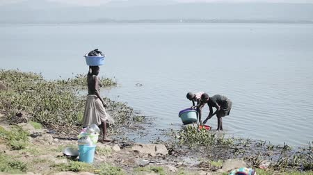 KENYA, KISUMU - MAY 20, 2017: Woman and her daughter wash dishes in lake, girl carry basin with clothes on head. Vídeos