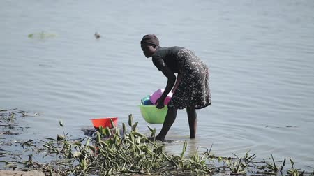 KENYA, KISUMU - MAY 20, 2017: Young african woman with her children washing dishes on the shore of the lake.