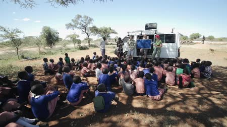 KENYA, KISUMU - MAY 20, 2017:African children sitting on the ground and listen to Caucasian men and women.