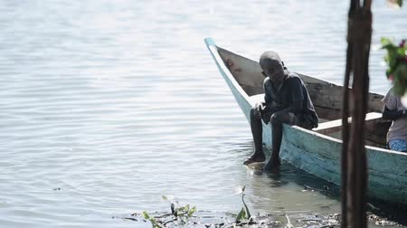 KENYA, KISUMU - MAY 20, 2017:Beautiful African boy is sitting in the boat on the shore of the sea and swinging his legs.