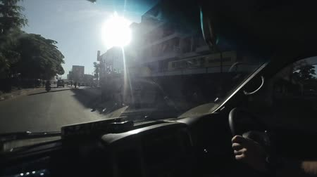 hátsó megvilágítású : KENYA, KISUMU - MAY 20, 2017:View from inside a moving car. Automobile is riding through the country road, turns on serpentine in bright sunny day in Africa. Stock mozgókép