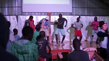 племя : KENYA, KISUMU MAY 20, 2017: Group of African teenagers, boys staying on the stage and showing dancing movements to children.