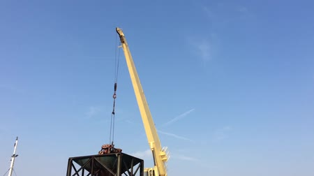 construction crane : Large yellow scoop Are scooping the white Urea chemical fertilizer From a pontoon boat to unload Stock Footage