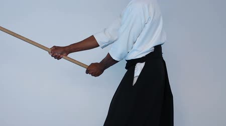defesa : Martial arts Master in black hakama practice martial arts with wooden jo stick