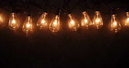 stary : Antique string light bulbs flickering and flashing on old dark background.