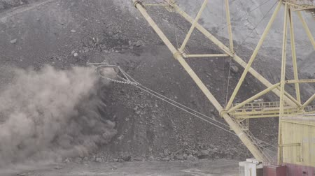 Dragline excavator walking on course throws dusty soil.
