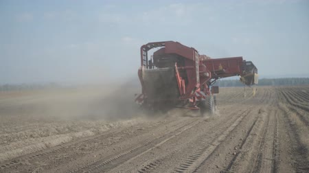 Red potato harvester travels across field and dusty.