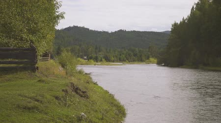 Wooden fence is on one side of large river, trees and mountain on other.