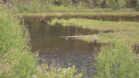 On swampy riverbank fisherman threw long bait and waits for fish.