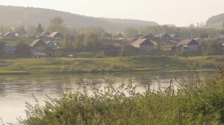 Wood village situated on banks of river in morning sun in Russia.