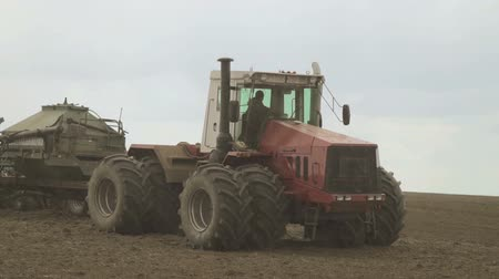 Tractor with eight wheels and a trailed hopper for grain on field.