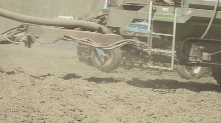 A tractor with a hitched sowing machine, rides on field closeup. Vídeos