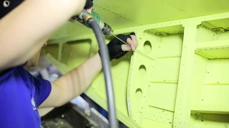 Worker drills holes in fuselage of aircraft with long driller. Vídeos
