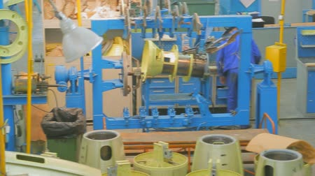 aeroespaço : Worker in blue overalls collects part of plane, sandwiched in a vise in mill plant.