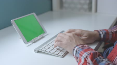 Male hands a plaid shirt typing on wireless keyboard with green screen of tablet. Vídeos
