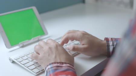 Male hands typing on wireless keyboard with a tablet with green screen on white desk.