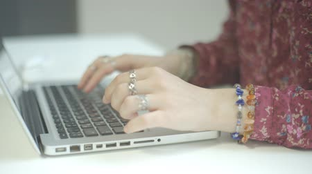 Beautiful female hands with rings typing on laptop.