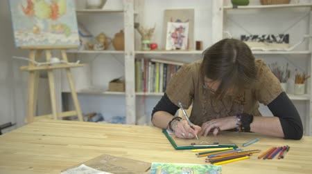 craftswoman : Woman is drawing picture or card sitting at desk with colorful pencils