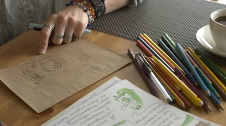 borracha : Woman artist draws illustrations for a childrens book with pencils.