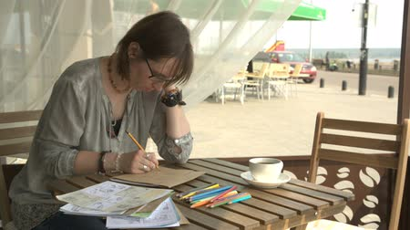 appreciation : Female artist is drawing picture sitting in cafe outside or terrace.