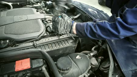 pil : Master unscrews air filter in hood of car at service center. Stok Video