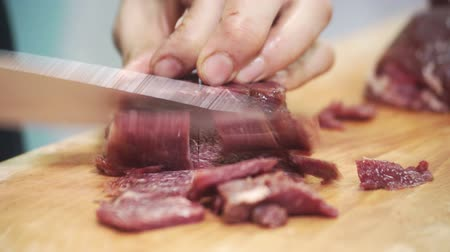 вырезка : On board meat being cut into chunks with a knife