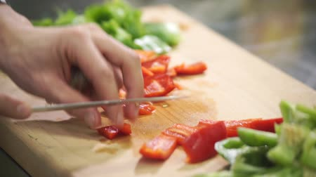 tábua de cortar : Chef cuts red green pepper on cutting board in industrial kitchen