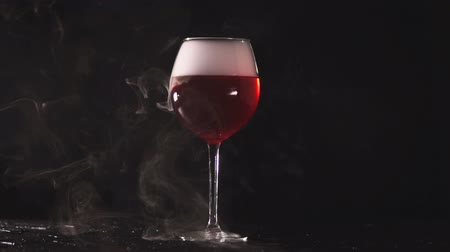 bílé víno : installation of smoke in glass with wine on black background.