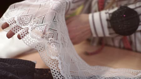 linen : Female tailor shows a broad band of white lace on his palms. Stock Footage