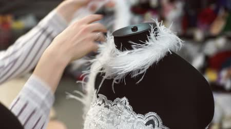 boa : Woman select accessories to white dress on mannequin for better image. There is snow clothes of pearl tulle with lace and rhinestone on black dummy.