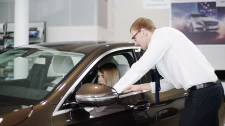 car rental : Manager in car center shows automobile to woman client in showroom. redhead tall male in white shirt, trousers, tie, glasses explains female possible features of car talks about store services in office. Stock Footage