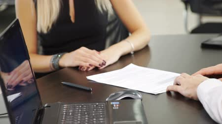holding document : Blond woman buyer signs contract to buy car in office center.