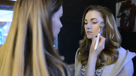 átalakítása : Visagiste does make up for model in beauty studio. Makeup artist making tender, pure look for young woman. Using fluffy shadow brush, professional stylist applies highlighter for a bit of definition in cheekbones, creating natural image.