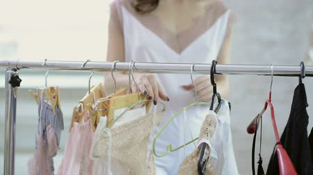 braçadeira : Woman in white clothing comes to rack with hangers to choose clothes in light room. Lady in white nightie moving hanger, take black lace underclothe to try.
