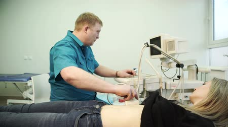 pregnant woman ultrasound : Redhead doctor making ultrasound of the abdomen of a young woman. In the city polyclinic, the doctor in blue uniform examines the abdomen of the patient, who lies motionless on the couch.