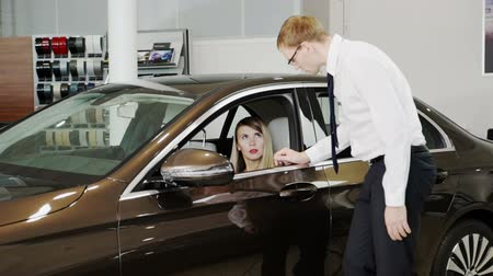 přihrádka : Salesman presenting executive class car to woman inside of show room. In slow motion dealer explains advantages of presentable automobile showing full details interior of vehicle to customer. Dostupné videozáznamy